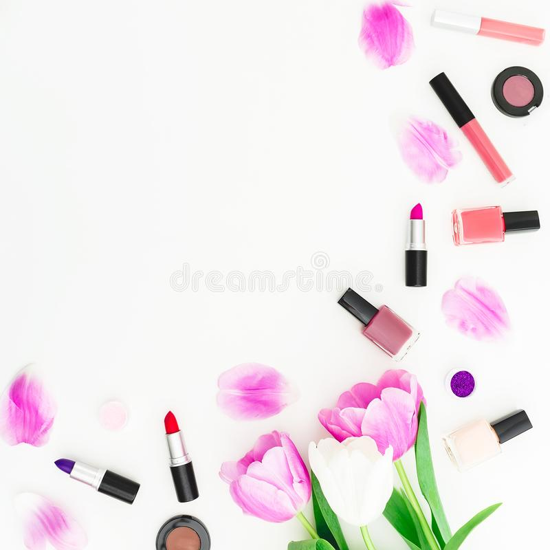 Frame made of tulips flowers and cosmetics on white background. Top view. Flat lay. Beauty feminine desk composition. stock photo