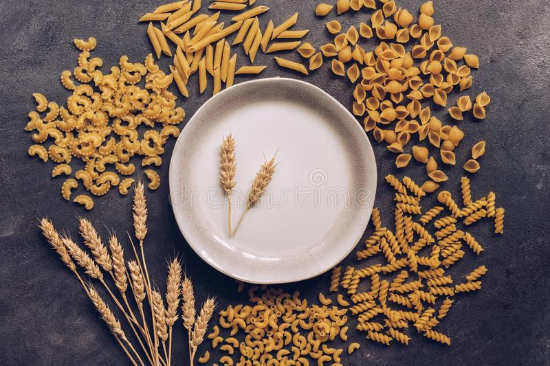 A frame made of various pasta, an empty plate decorated with spikelets of wheat on a dark background. Top view, place for text royalty free stock image