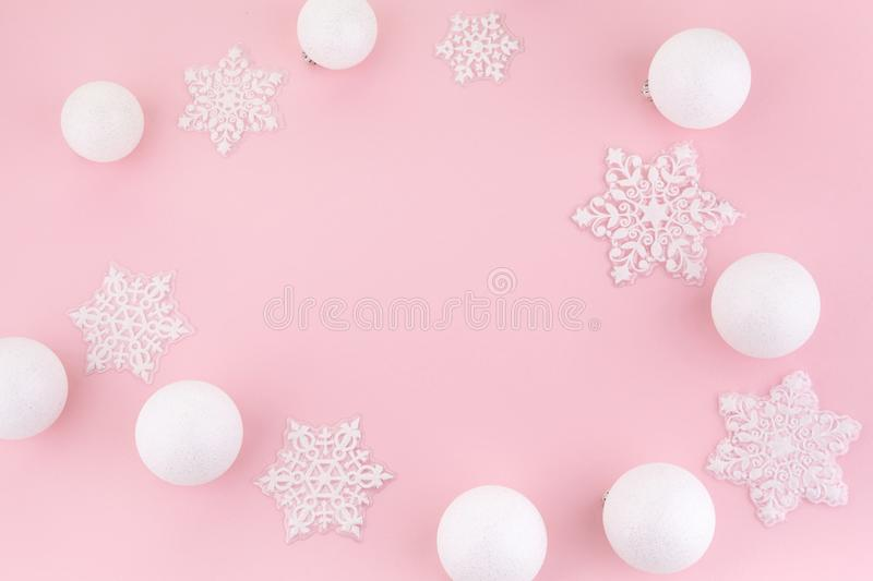 Frame made of white christmas decoration with christmas glass balls on pink background. flat lay, top view royalty free stock image