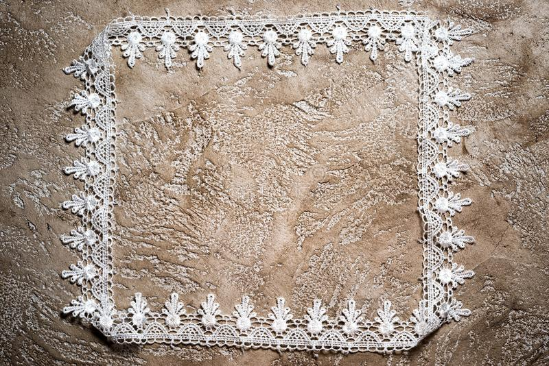 Frame. Made of white lace carelessly stacked on a neutral beige grunge concrete background stock photography