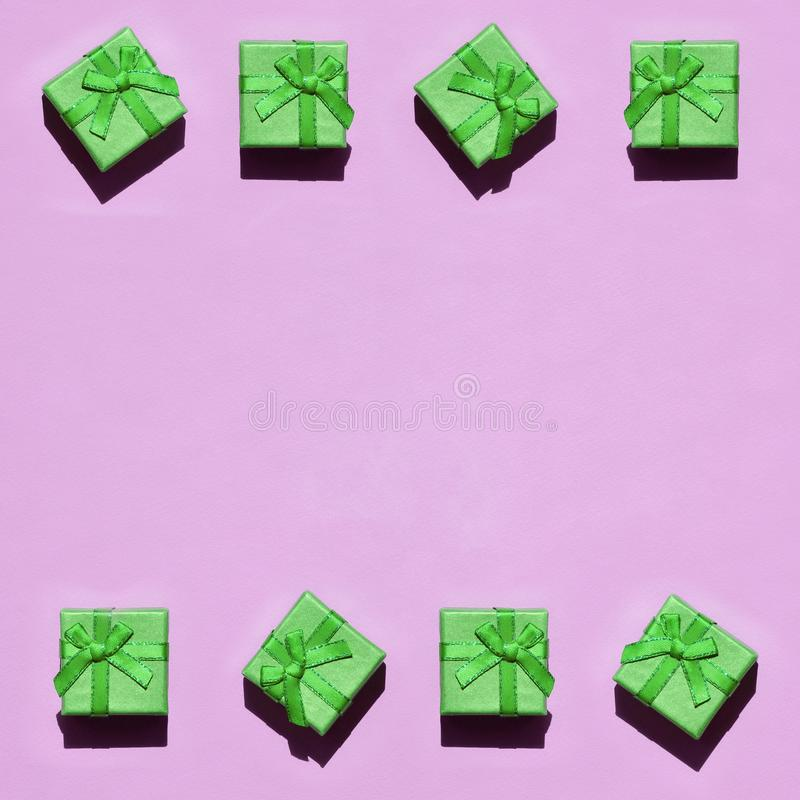 Frame of many small green gift boxes on texture background of fashion trendy pastel pink color paper royalty free stock photography