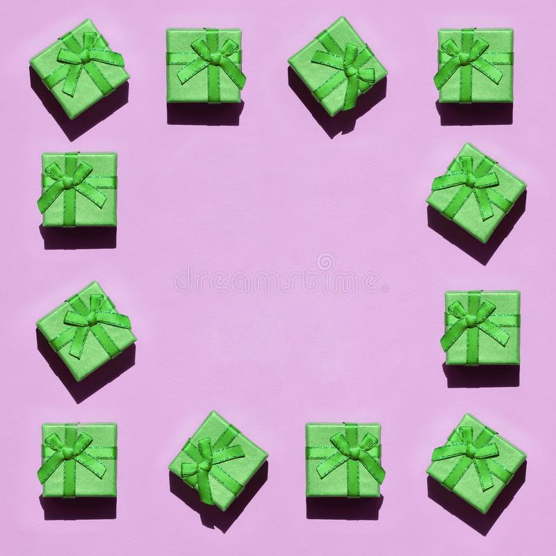 Frame of many small green gift boxes on texture background of fashion trendy pastel pink color paper royalty free stock images