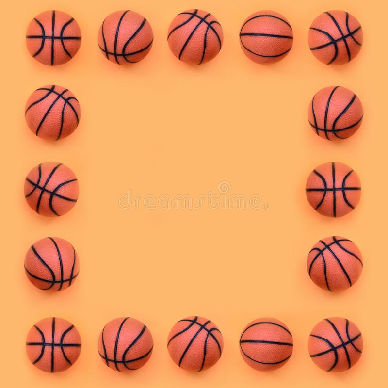 Frame of a many small orange balls for basketball sport game lies on texture background of fashion pastel orange color paper in stock image