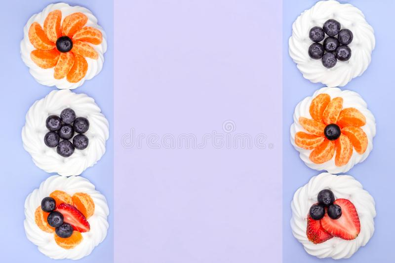 Frame of meringue with blueberries, strawberries and tangerines on a lavender background. Top view royalty free stock images