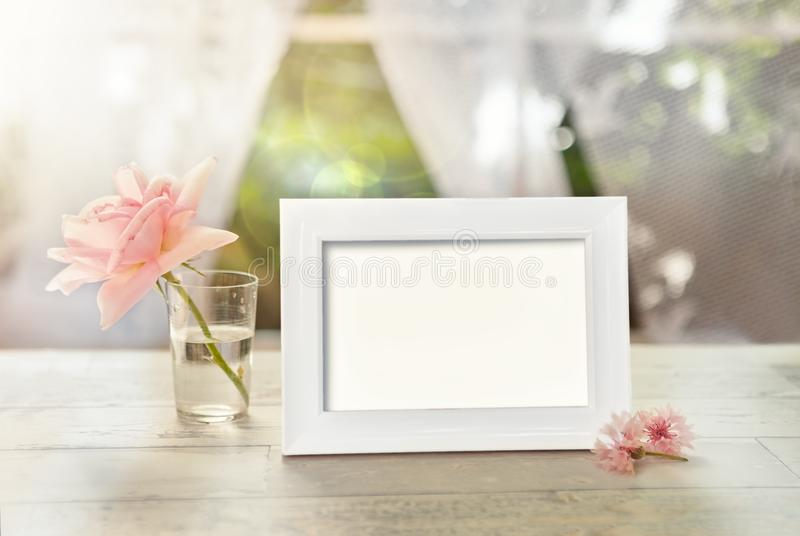 Frame mockup with flower in glass. And petal on the table stock images
