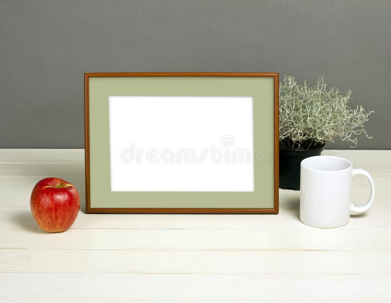 Frame mockup with plant pot, mug and apple on wooden shelf. Empty frame mock up for presentation design. Template framing for modern art stock photo