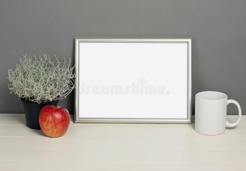 Frame mockup with plant pot, mug and apple on wooden shelf. Empty frame mock up for presentation design. Template framing for modern art stock images