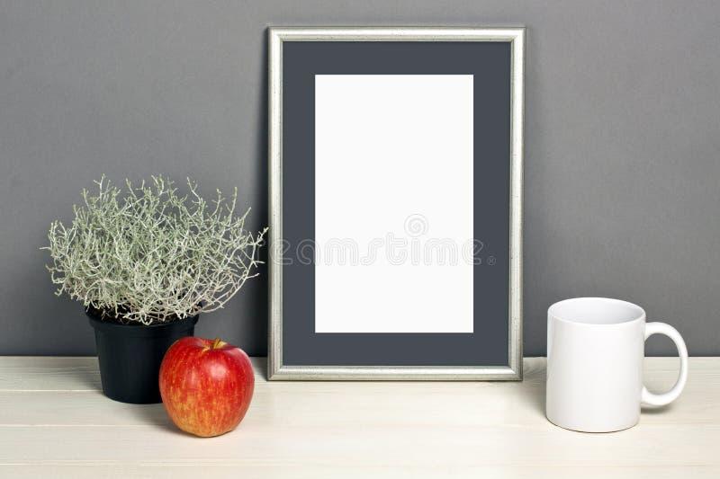 Frame mockup with plant pot, mug and apple on wooden shelf. Empty frame mock up for presentation design. Template framing for modern art royalty free stock photography