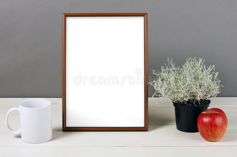 Frame mockup with plant pot, mug and apple on wooden shelf. Empty frame mock up for presentation design. Template framing for modern art royalty free stock image