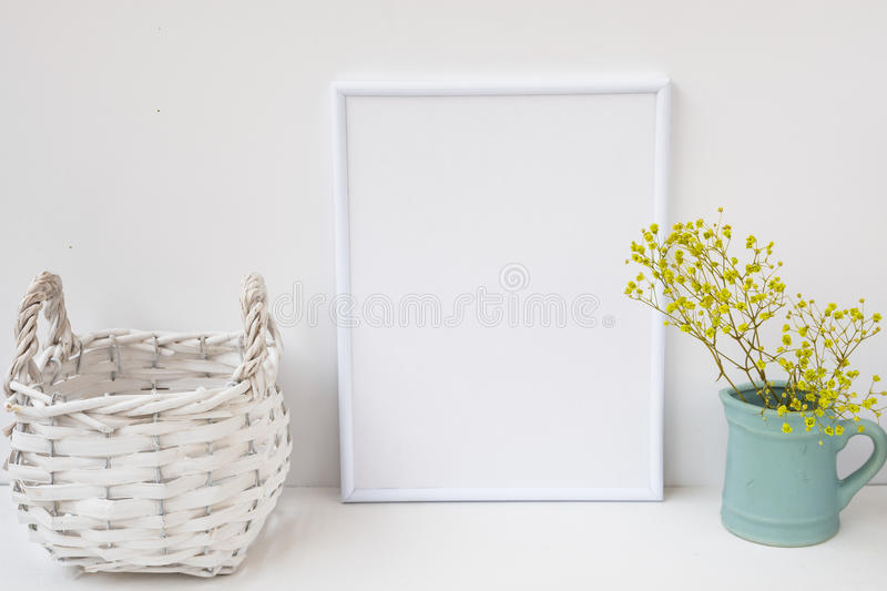 Frame mockup, wicker basket, pitcher with flowers on white background, styled image for product marketing royalty free stock photography