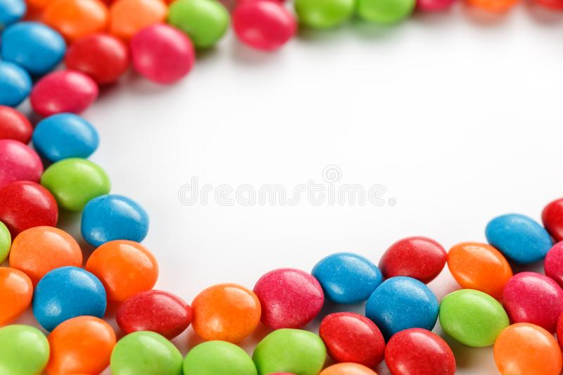 Frame of multi-colored candies close up. Rainbow colored dragee multicolored glaze on a white background. Bright colours stock photography