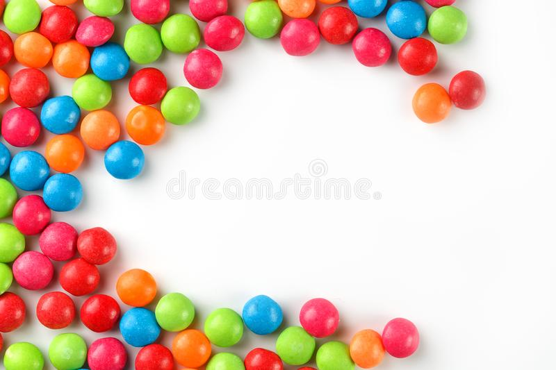 Frame of multi-colored candies close up. Rainbow colored dragee multicolored glaze on a white background. Bright colours stock photos
