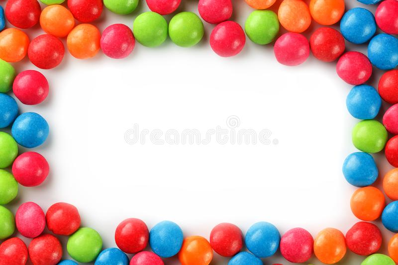 Frame of multi-colored candies close up. Rainbow colored dragee multicolored glaze on a white background. Bright colours stock photo