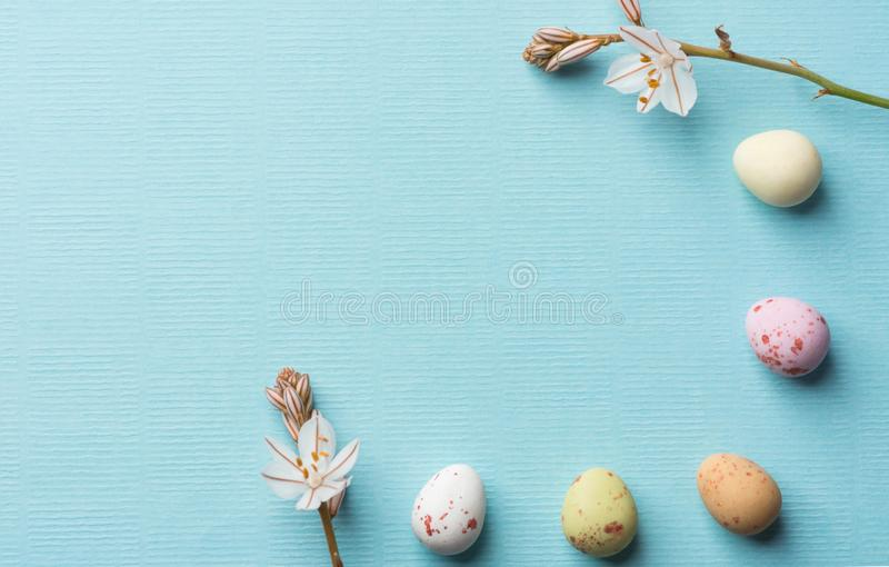 Frame from multicolored speckled chocolate eggs spring field flowers on light blue background with linen paper texture. Easter. Greeting card poster banner stock images