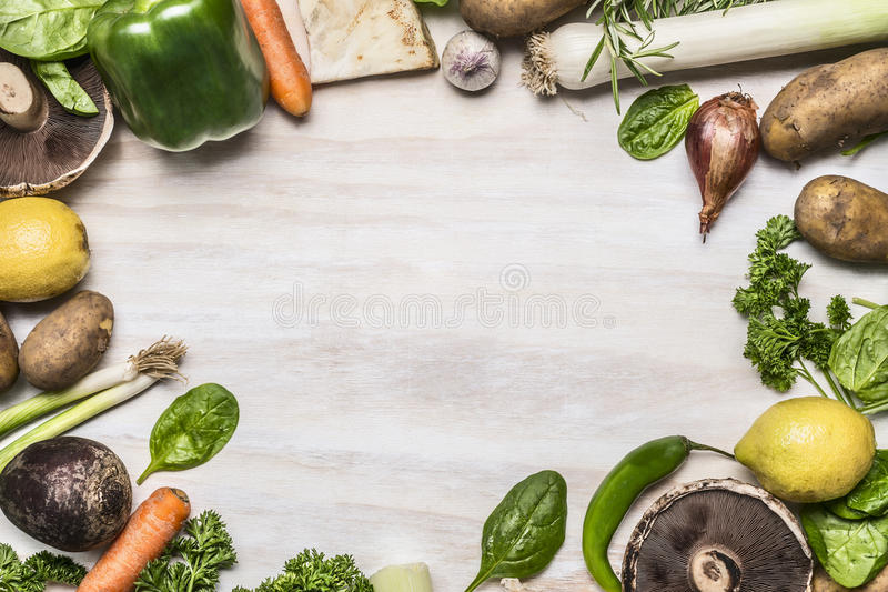 Frame of mushrooms onion potato greens lemon pepper garlic on white rustic wooden background top view. Frame of mushrooms onion potato greens lemon pepper garlic royalty free stock images
