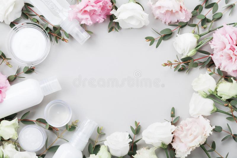 Frame from natural cosmetic and flowers on pastel table top view. Flat lay style. royalty free stock images