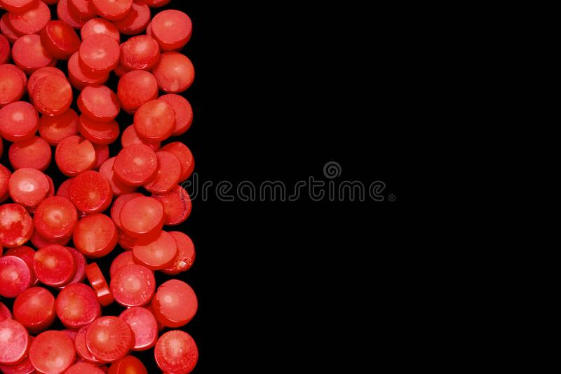 Natural red coral flat beads as red blood cells isolated on a black background. Frame of natural red coral flat circled beads isolated on a black background stock image