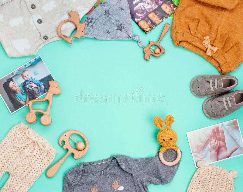 Frame of newborn baby`s clothing on turquoise background stock photos