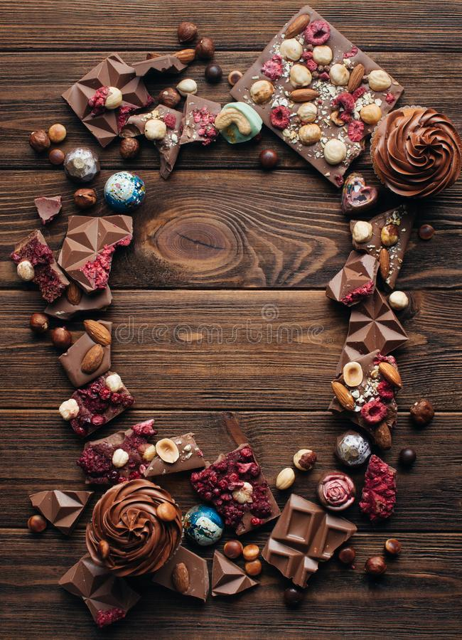 Free Frame Of Broken Bars Of Milk Chocolate On Rustic Wooden Background Stock Image - 112774221