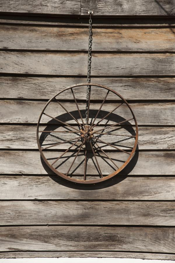 An old wagon wheel. The frame of an old wagon carriage wheel hung by a chain royalty free stock images