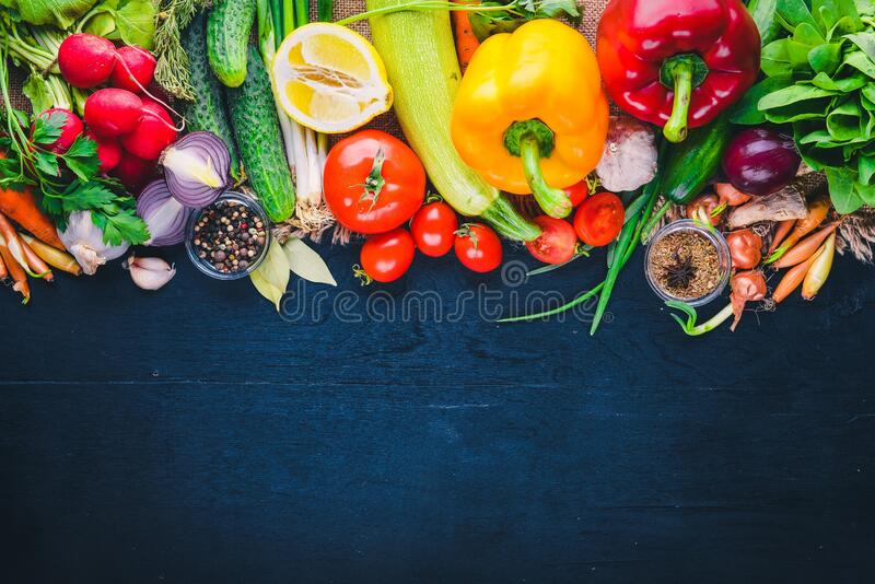 Frame of organic food. Fresh raw vegetables and spices. On a wooden chalkboard stock photos