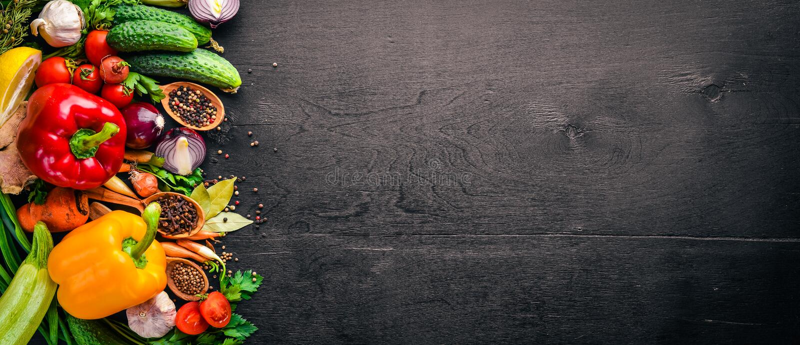 Frame of organic food. Fresh raw vegetables and spices. On a wooden chalkboard stock image