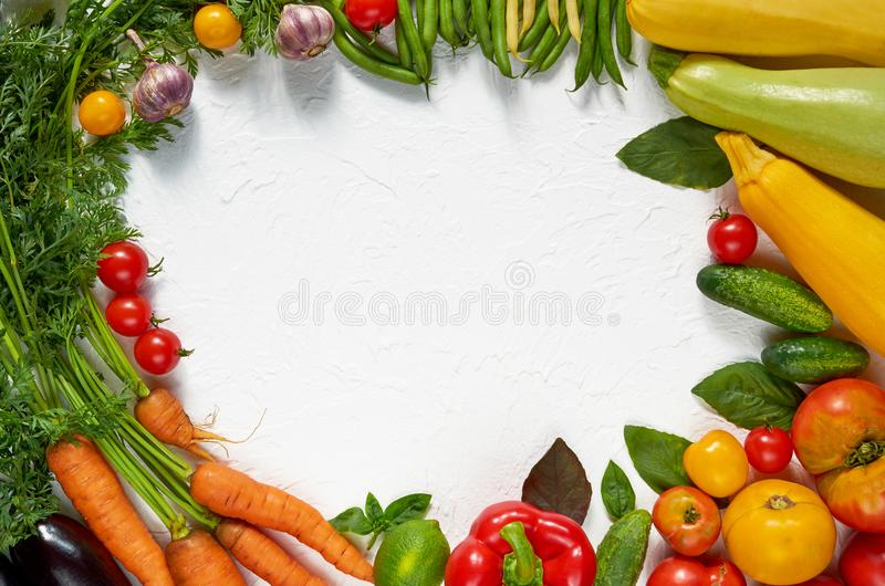 Frame of organic raw vegetables, herbs and spices on the white table. Healthy vegetarian diet food background. Top view. With copy space for text royalty free stock images