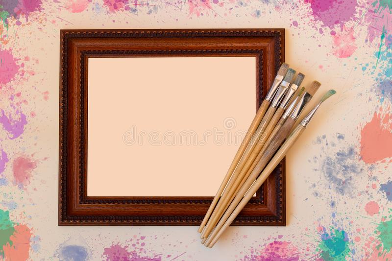 Frame with paint brushes on beige background stock images