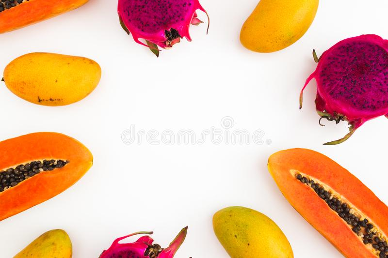 Frame of papaya, mango and dragon fruits on white background. Flat lay. Top view. Tropical fruit. Concept royalty free stock photos