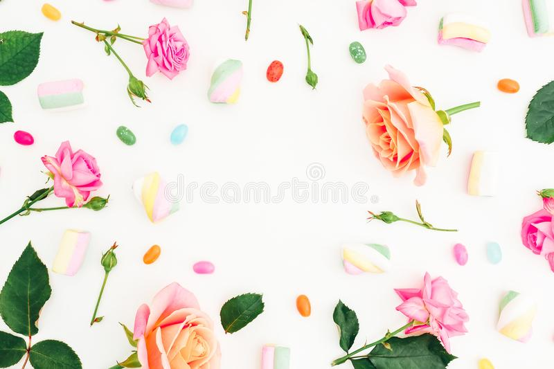 Frame pattern with roses flowers, buds, leaves and marshmallow with candy on white background. Flat lay, top view. Summer backgrou. Frame pattern with roses stock photos