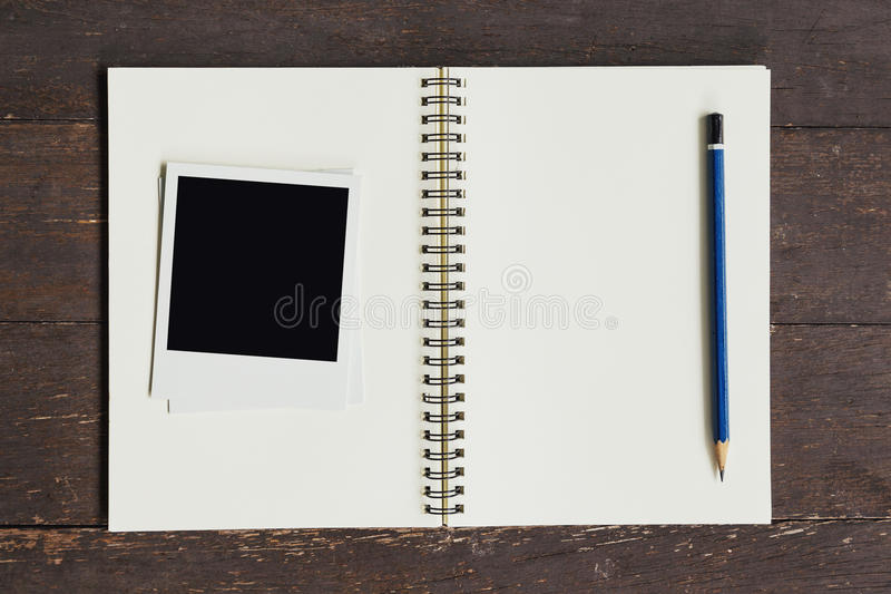 Frame photo and brown book on wood table stock images