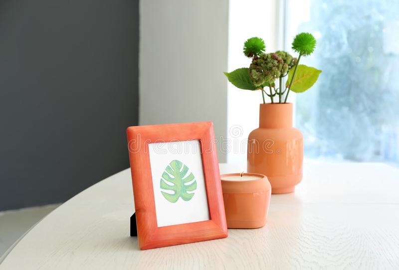 Frame with picture of green leaf and burning candle on white table royalty free stock photos
