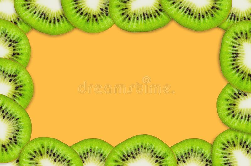 Frame with pieces of sliced tasty beautiful ripe fresh kiwi fruit on orange table in kitchen. Top view. Cooking concept royalty free stock images