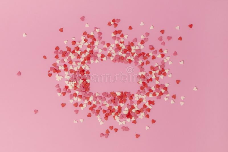 Frame on a pink background made of small sweet multi-colored candy hearts. Copy space. View from above royalty free stock images