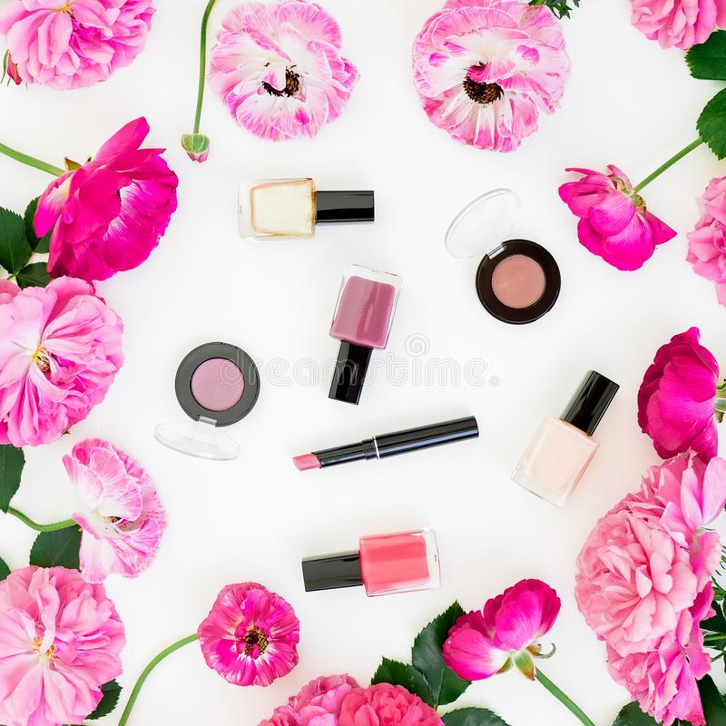 Frame with pink flowers and feminine cosmetics on white background. Flat lay stock photos