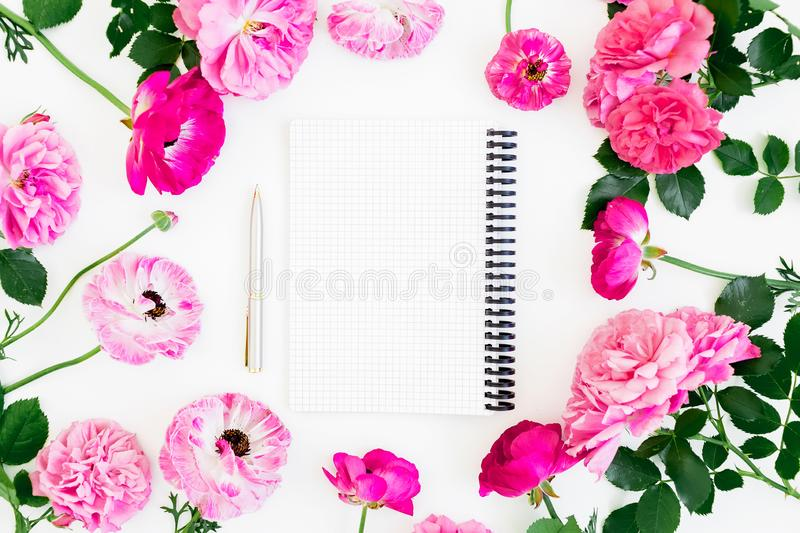 Frame of pink ranunculus flowers, roses and notebook with pen on white background. Lifestyle composition. Flat lay, top view. Frame of pink ranunculus flowers royalty free stock photography