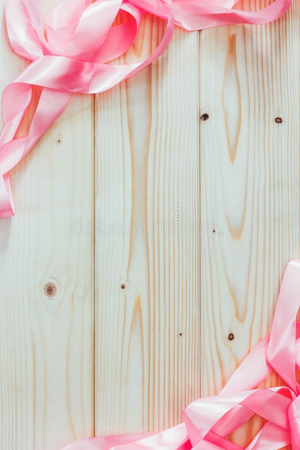 Frame of pink ribbons on natural wooden background with copy space. Mock up for text, for phrases, for lettering, for congratulations royalty free stock image