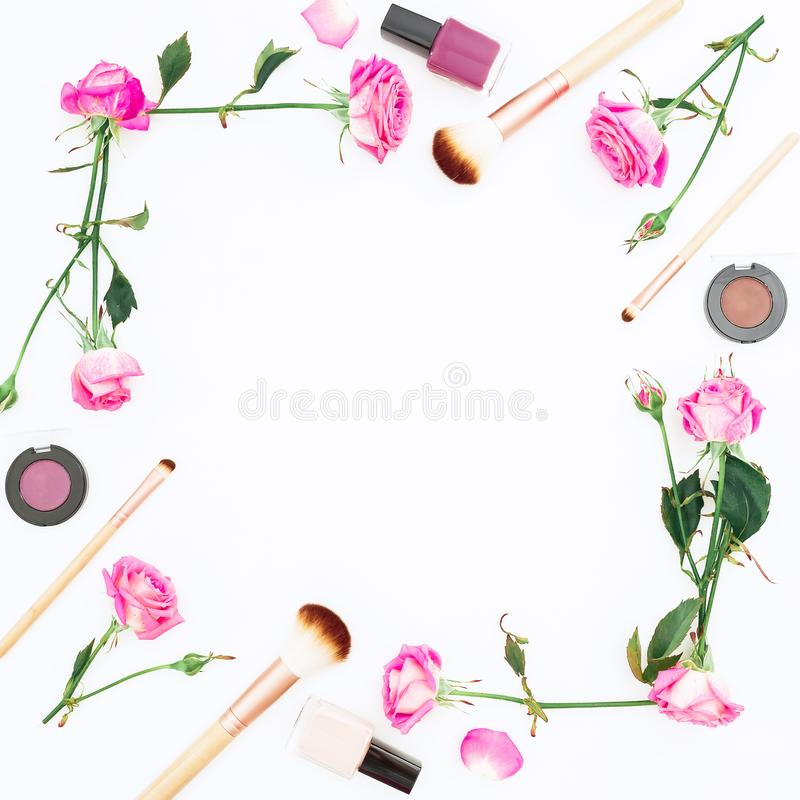 Frame with pink roses and feminine cosmetics on white background. Beauty concept, woman day. Flat lay, Top view. stock photography