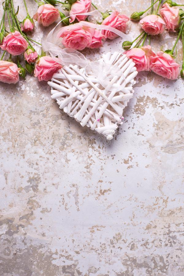 Frame from pink roses flowers and decorative heart. On grey vintage textured background. Floral still life. Selective focus. Vertical image royalty free stock images