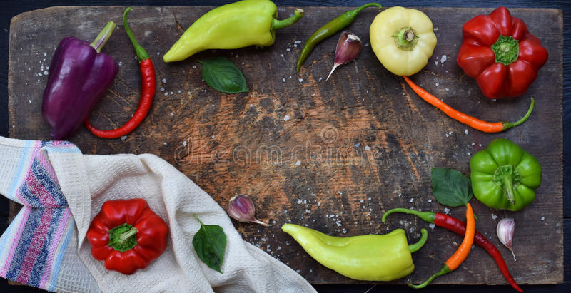 A frame for recipe from different varieties of sweet and hot pepper on a wooden background. Food border. Copy space.  royalty free stock images