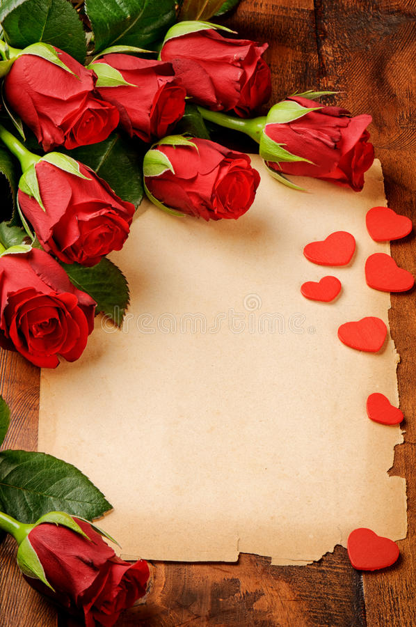 Frame with red roses and vintage paper stock photo