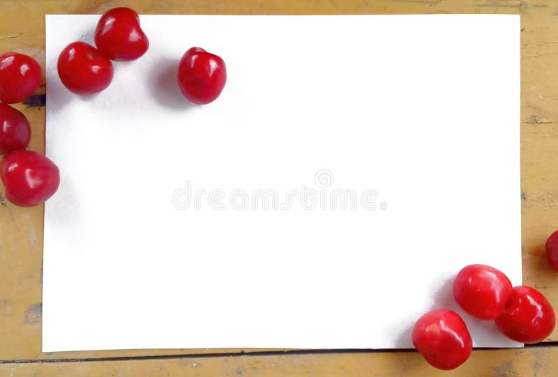 Frame of ripe red cherries on a yellow old table with peeling paint. Berries lie on white clean watercolor paper with copy space. The idea for mocap, text royalty free stock image