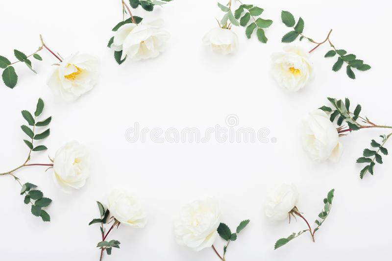 Frame of rose flowers and green leaves on white table top view. Beautiful wedding pattern in flat lay styling. Frame of rose flowers and green leaves on white stock images