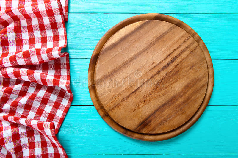 Frame of round cutting board and red plaid tablecloth. Blue wooden background in the restaurant. Top view. Frame of round cutting board and red plaid tablecloth royalty free stock image