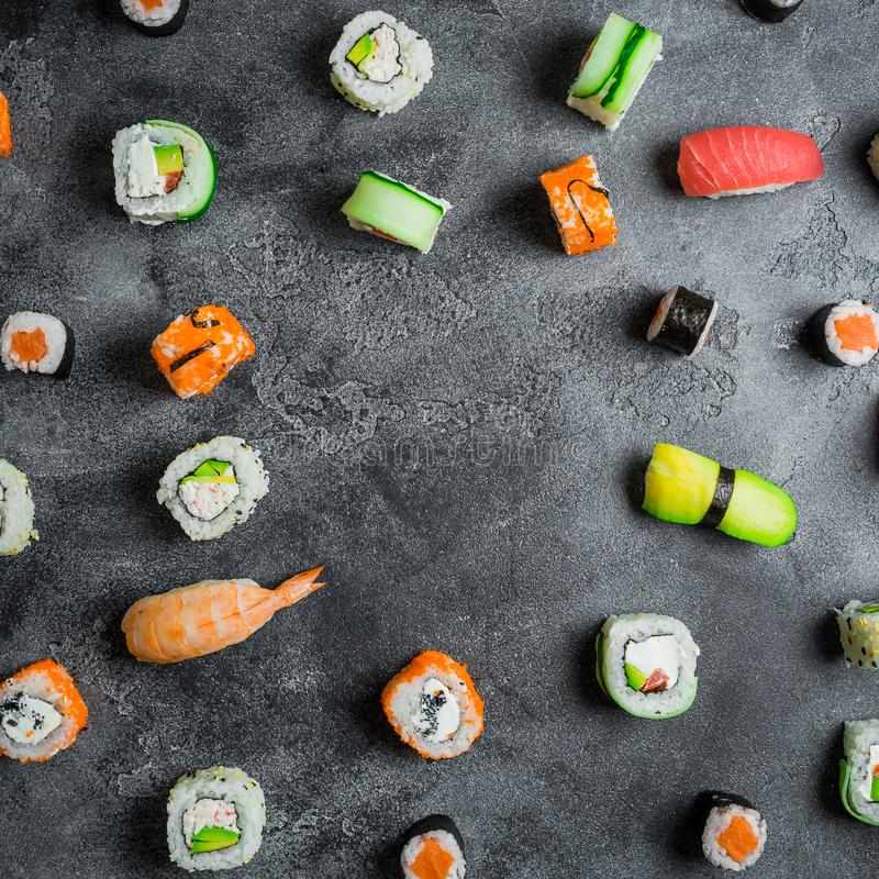 Frame with set of Japanese food on dark background. Sushi rolls, nigiri, raw salmon steak and avocado. Flat lay. Top view royalty free stock photos