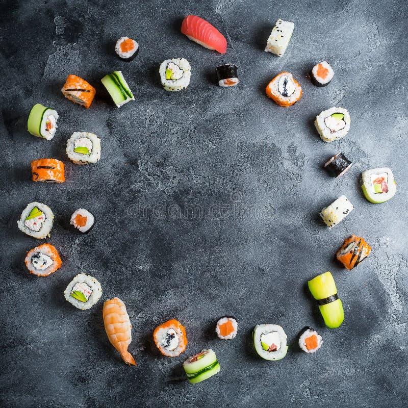 Frame with set of Japanese food on dark background. Sushi rolls, nigiri, raw salmon steak, rice and avocado. Flat lay. Top view stock photo