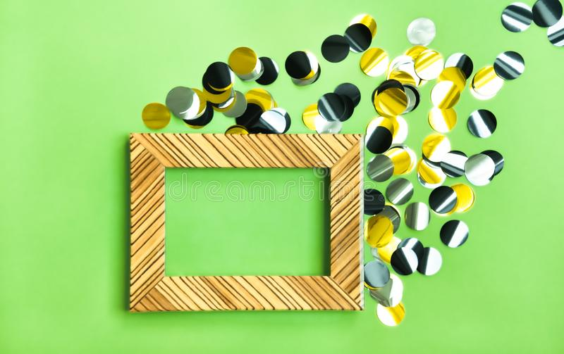 Frame and shiny confetti. Shiny golden, silver and black confetti and light wooden frame on yellow green background. Festive modern concept stock image
