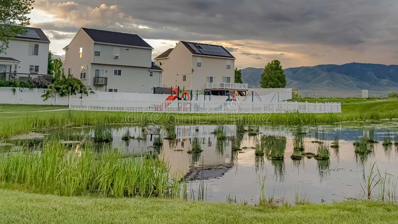 Frame Shiny pond playground and multi storey homes surrounded by vast grassy terrain. Panorama frame Shiny pond playground and multi storey homes surrounded by stock photo