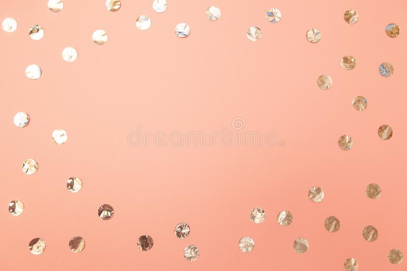 Frame of shiny silver confetti on pastel millennial pink paper background. Concept of holiday, birthday, celebration, beauty. stock photo