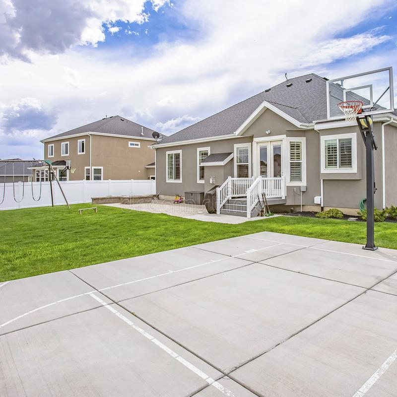 Frame Square Basketball court and swings on the spacious yard of a single storey family home. Overhead is a picturesque vibrant blue sky with fluffy clouds royalty free stock image